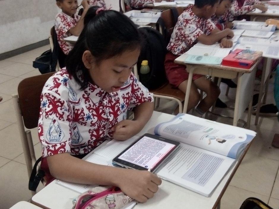 Salah seorang siswa membaca dengan tablet
